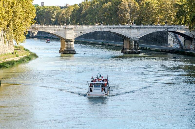 Kajen av floden Tiber i Rome, en bro och en grupp av utländska turister på ett fartyg turnerar och arkitektoniska monument och ch royaltyfri fotografi