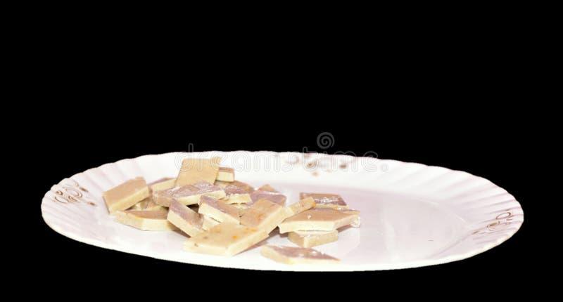 Kaju Katli是印度甜点做使用腰果糖的金刚石形状,并且mava,在喜怒无常的背景的一块板材服务 图库摄影