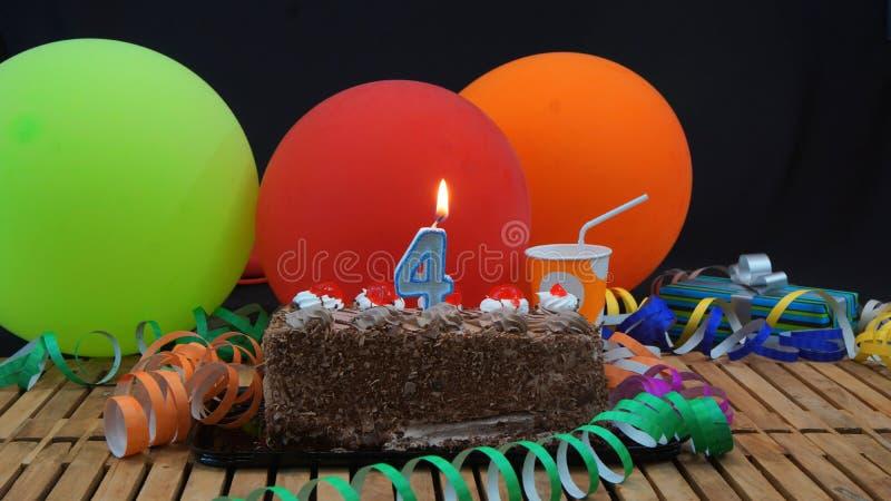 Kaka för chokladfödelsedag 4 med stearinljus som bränner på den lantliga trätabellen med bakgrund av färgrika ballonger fotografering för bildbyråer