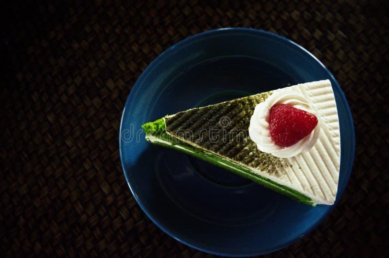 Kaka för grönt te som förläggas på en blå platta royaltyfria foton