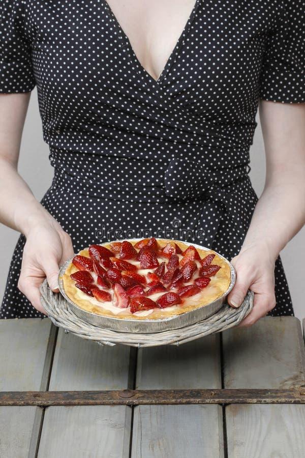 Kaka för jordgubbe för kvinnainnehavrunda arkivfoton