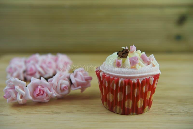 Kaka för kopp för valentindag romantisk med träförälskelsehjärtagarnering överst och pappers- rosor för rosa färger royaltyfria foton
