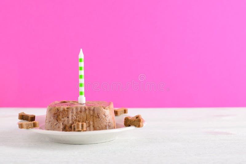 Kaka för lycklig födelsedag för hund från våta mat och fester med stearinljuset på rosa bakgrund arkivfoto