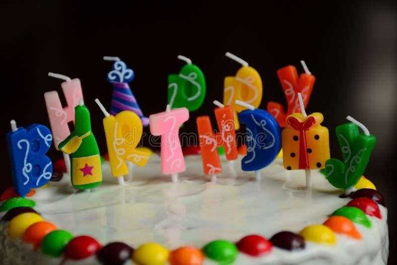 Kaka för lycklig födelsedag med stearinljus på svart bakgrund fotografering för bildbyråer
