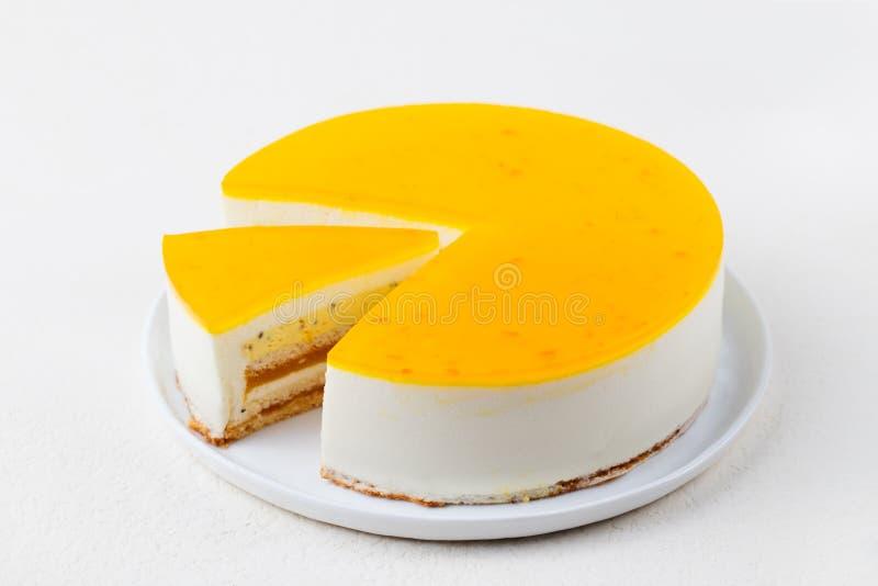 Kaka för passionfrukt, mousseefterrätt på en vit platta kopiera avstånd arkivfoton