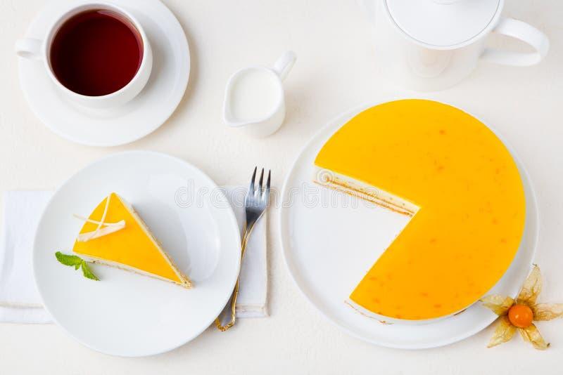 Kaka för passionfrukt, mousseefterrätt på en vit platta med kopp te Top beskådar royaltyfri bild