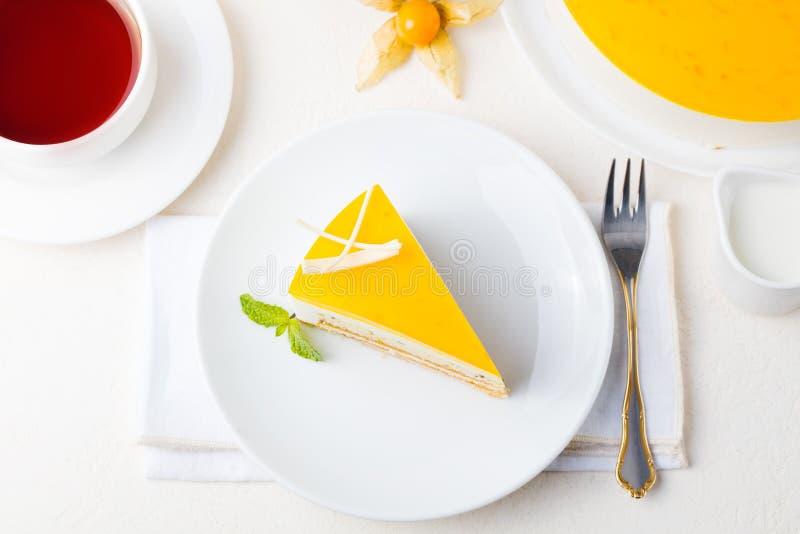 Kaka för passionfrukt, mousseefterrätt på en vit platta med kopp te Top beskådar fotografering för bildbyråer