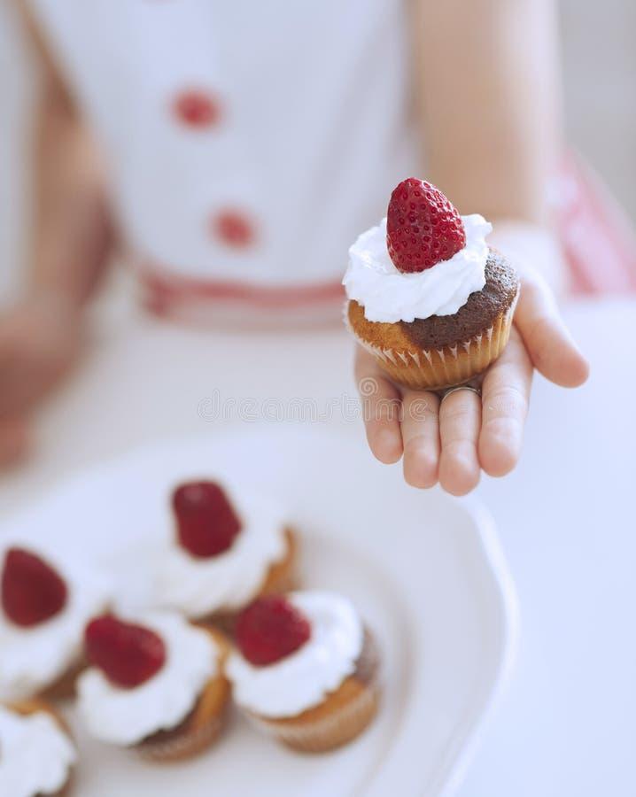 Kaka för ung flickainnehavkopp royaltyfria foton
