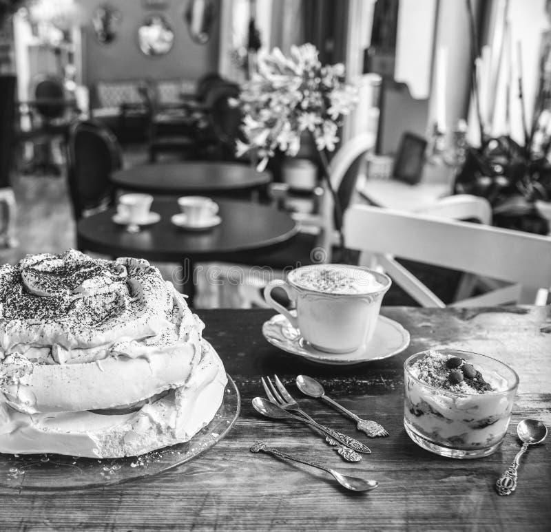 Kaka-maräng, efterrätt- och lattekaffe på en tappningtabell i ett kafé i en retro stil royaltyfri foto