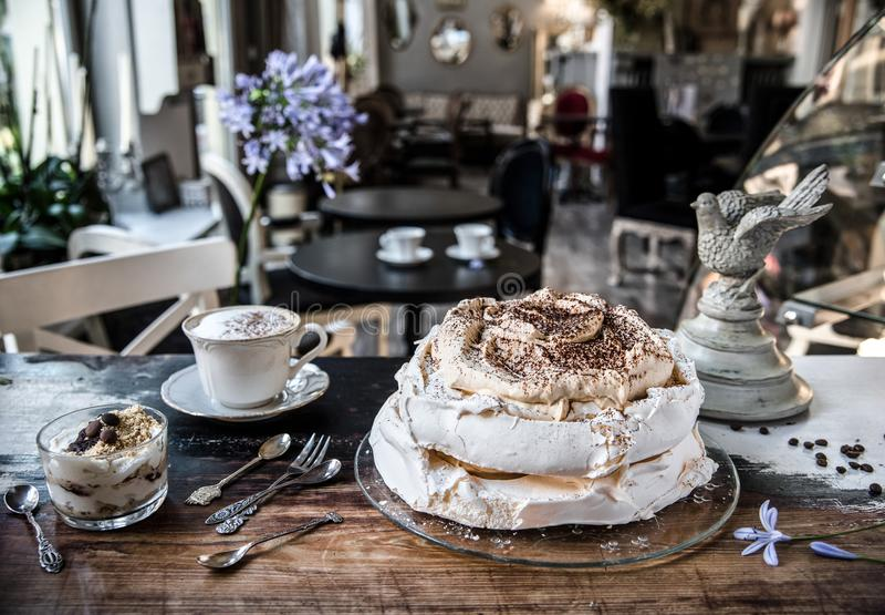 Kaka-maräng, efterrätt- och lattekaffe på en tappningtabell i ett kafé i en retro stil royaltyfri fotografi