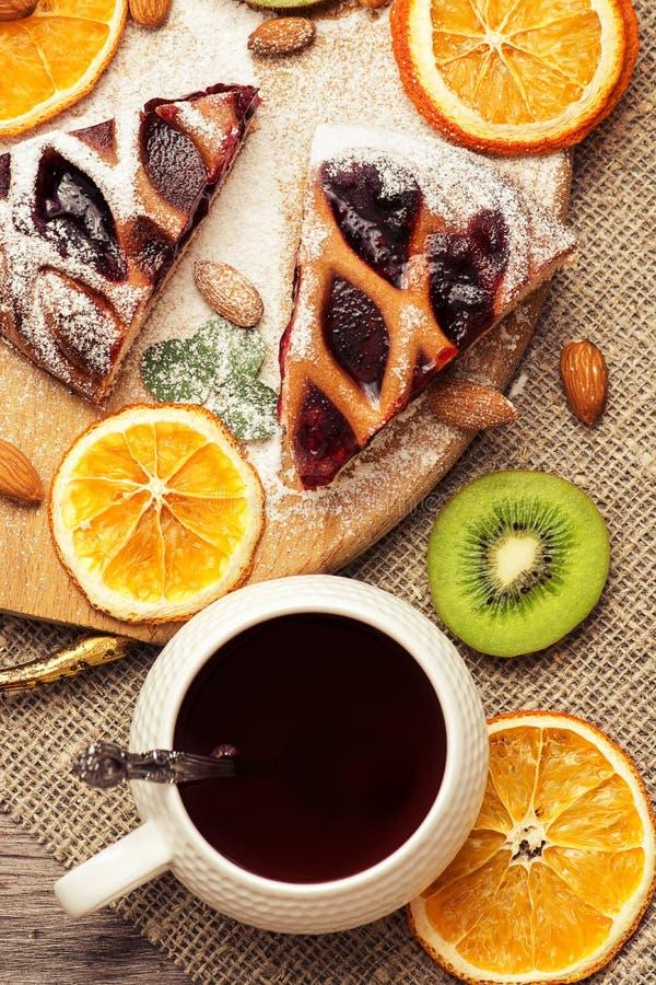 Kaka med bär och kopp te Torkade apelsiner, kiwi och mandlar royaltyfri bild
