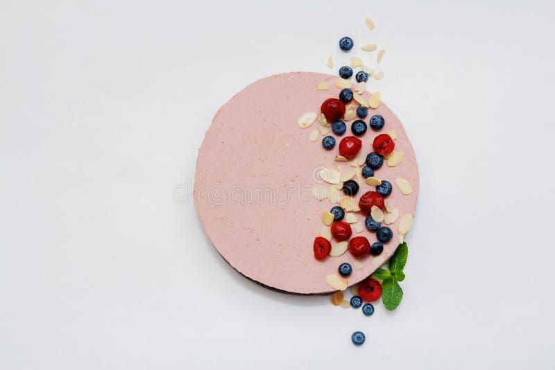 Kaka med den piskade rosa kräm, blåbär, björnbäret och hallonet på vit bakgrund Top beskådar Bild för en meny eller royaltyfria foton