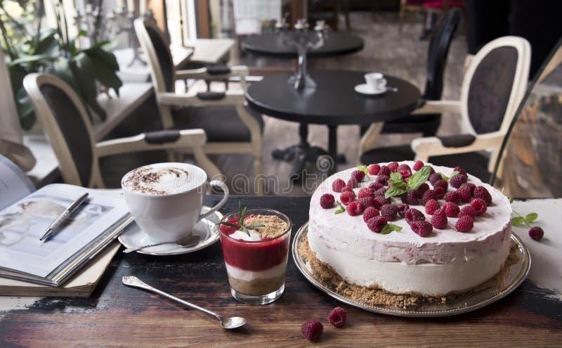 Kaka med hallon, kaffelatte, jordgubbeefterrätten och boken på en gammal tabell i retro kafé arkivfoto