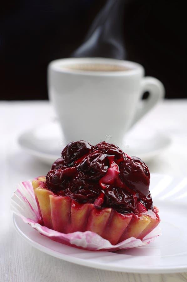 Kaka med körsbäret och koppen kaffe royaltyfri foto