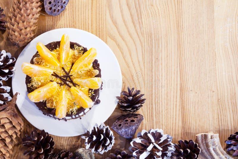Kaka med mandarinskivor som omges av grankottar royaltyfria foton