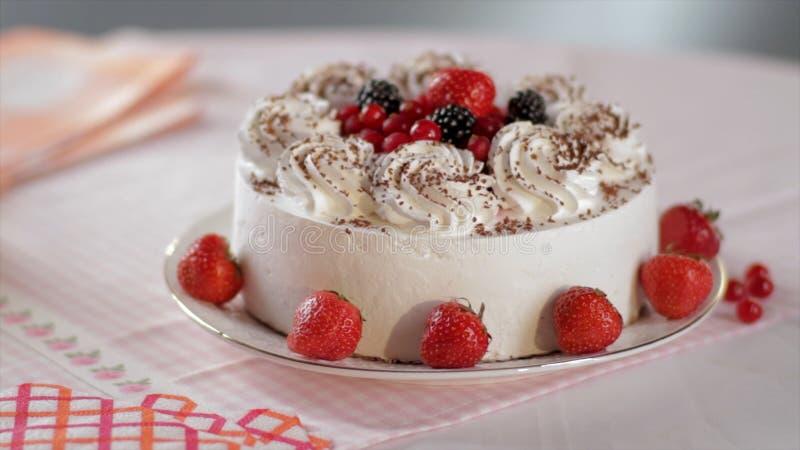 Kaka med piskade kräm och jordgubbar på en ställning, närbild plats Skivade inget bakar dekorerad jordgubbeostkaka royaltyfria foton