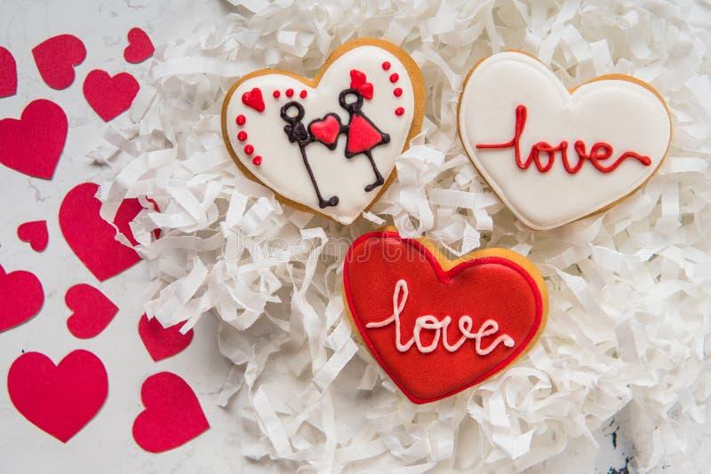 Kakahjärtor med vit och röd isläggning för dag för valentin` s royaltyfria foton