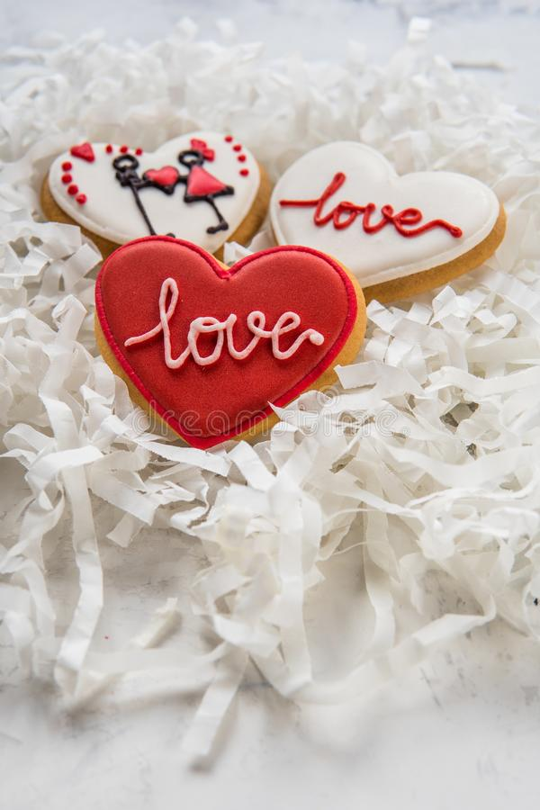 Kakahjärtor med vit och röd isläggning för dag för valentin` s royaltyfria bilder
