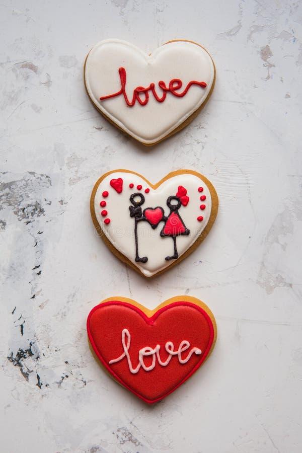 Kakahjärtor med vit och röd isläggningförälskelse för dag för valentin` s royaltyfria foton