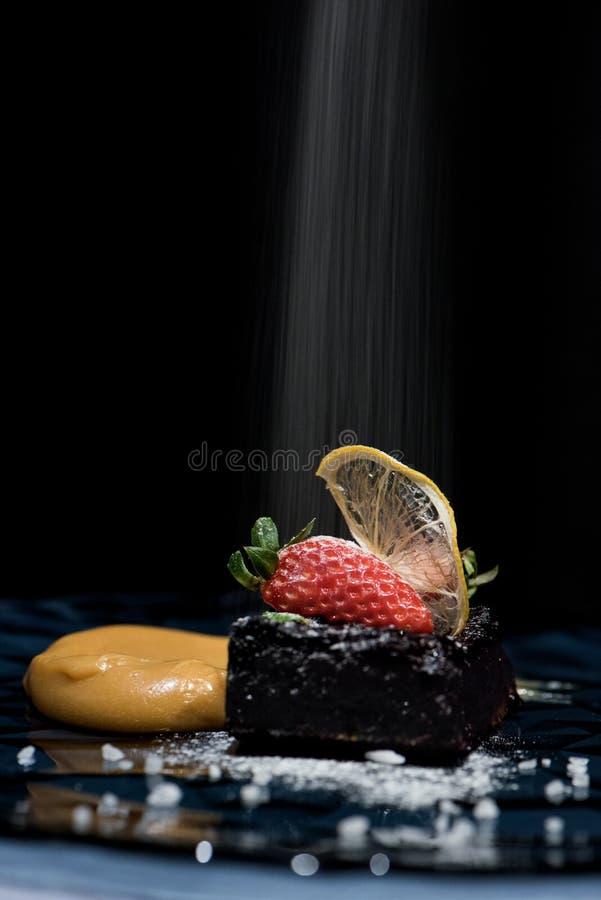 Kakan för den svarta vinbäret med rimmad karamell och jordgubben med fallande surt socker pudrar arkivfoto