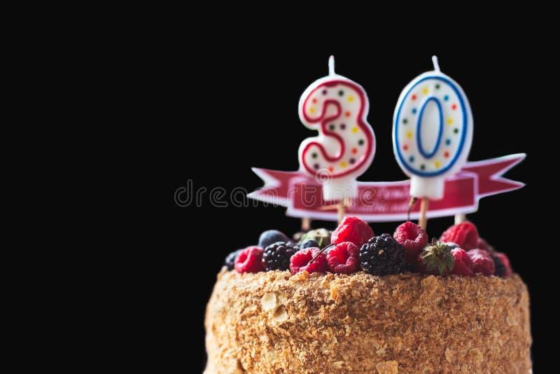 Kakan för hallonbjörnbärfödelsedagen med stearinljus numrerar 30 på svart bakgrund och copyspace för din text arkivbilder
