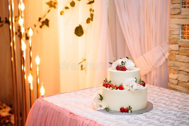 Kakan för kräm för brölloptre-berättelsen vit är på tabellen Efterrätten dekoreras med bär av mogna röda jordgubbar och fotografering för bildbyråer