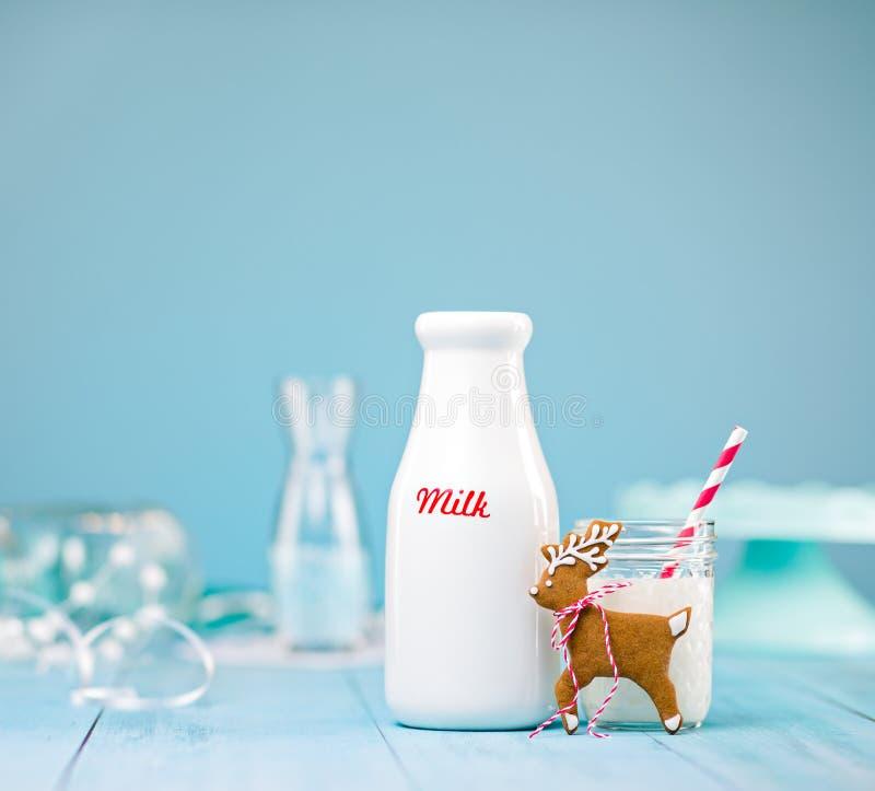 Kakan för pepparkakarenjul med mjölkar över blått royaltyfri bild