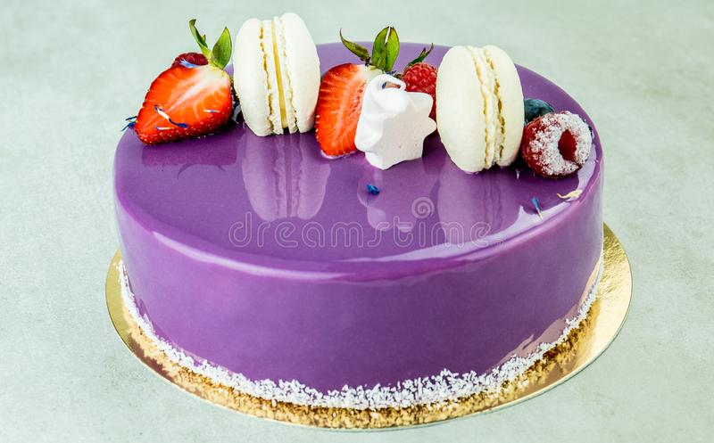 Kakan som gjordes av purpurfärgad choklad, dekorerade med hallon och jordgubbar arkivfoton