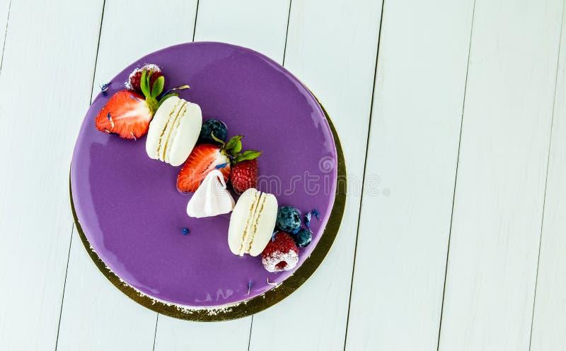 Kakan som gjordes av purpurfärgad choklad, dekorerade med hallon och jordgubbar arkivbild