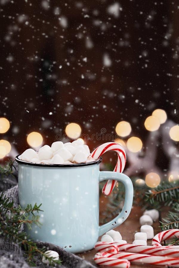 Kakao mit Eibischen und Zuckerstangen mit fallendem Schnee stockfoto