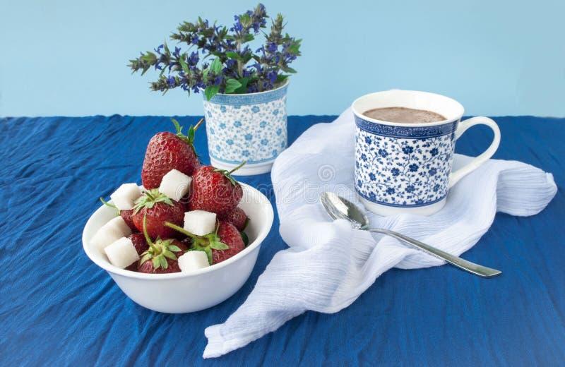 Kakao und Erdbeere mit Zucker auf einem Hintergrund eines Blumenstraußes der Blumen stockfotos