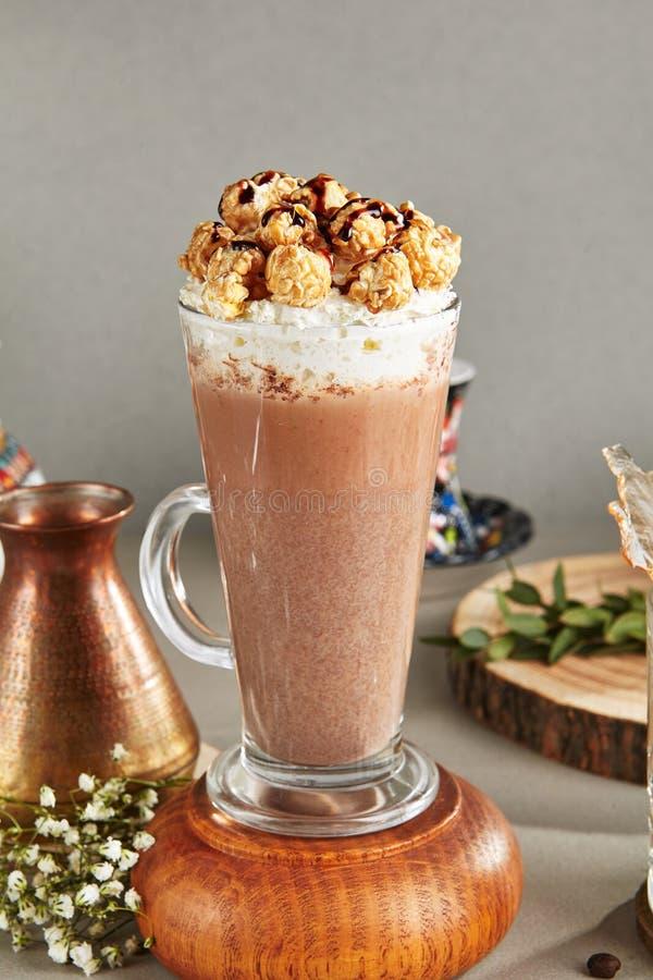 Kakaodrink med piskat kräm- och karamellpopcorn i högväxt exponeringsglas arkivbild