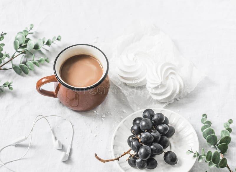 Kakaokopp, druvor och maräng för lägenhet lekmanna- på en vit bakgrund Morgonfrukostinspiration arkivbild