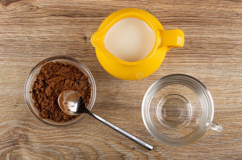 Kakaopulver in der Schüssel, Löffel, Krug Milch, Schale auf Holztisch Beschneidungspfad eingeschlossen stockbild