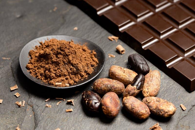 Kakaopulver i en svart keramisk maträtt bredvid grillat skalade och unpeeled kakaobönor, chokladshavings och en tjock skiva av mö arkivfoton
