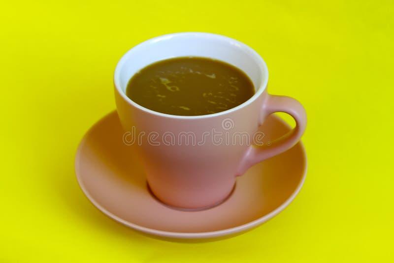 Kakaowy napój w menchia kubku na yelow tle zdjęcie stock