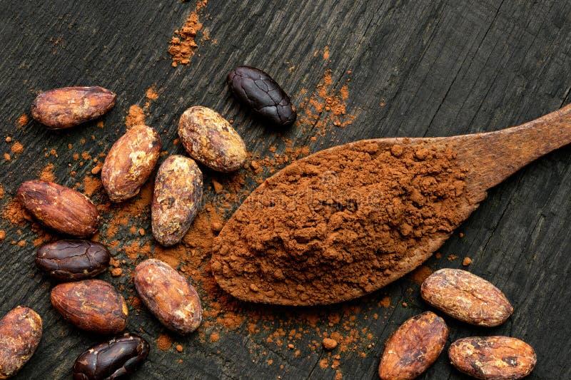 Kakaowy proszek na drewnianej łyżce odizolowywającej na czarnej nieociosanej drewno desce z góry Rozlewający kakaowy, piec kakao  obrazy royalty free