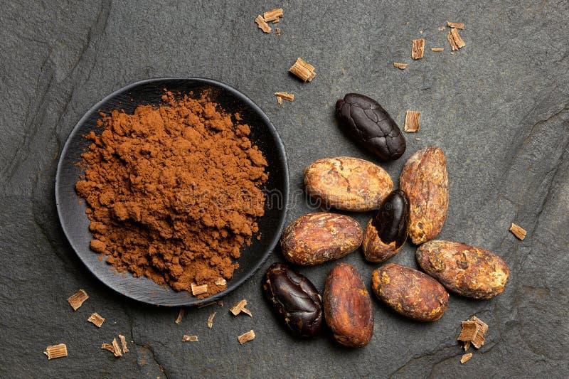 Kakaowy proszek w czarnym ceramicznym naczyniu obok piec kakaowych fasoli, czekoladowi golenia na czerni i krytykujemy od zdjęcia royalty free