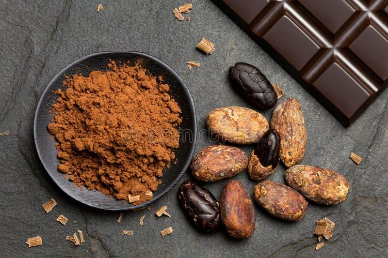 Kakaowy proszek w czarnym ceramicznym naczyniu obok piec kakaowych fasoli, czekoladowych goleń i cegiełki zmrok obranych i unpeel fotografia stock