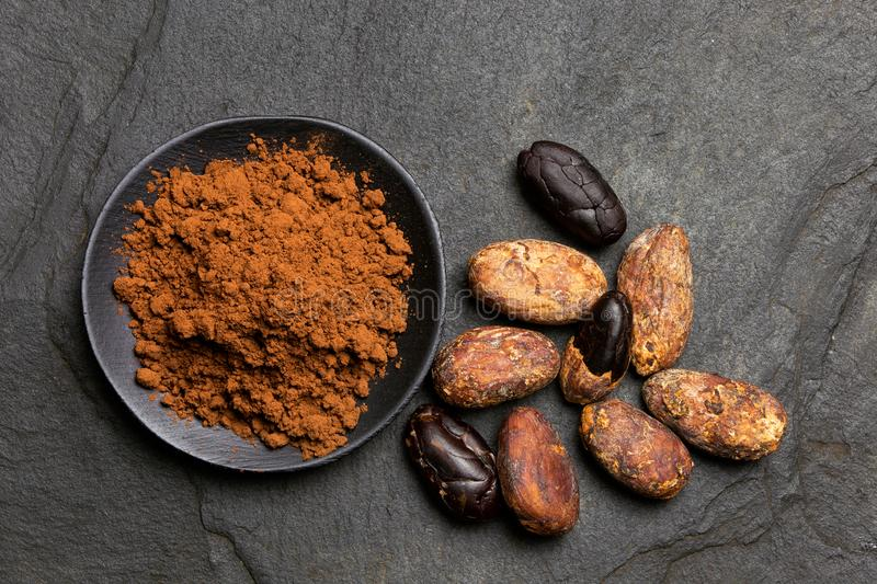 Kakaowy proszek w czarnym ceramicznym naczyniu obok piec obranych i unpeeled kakaowych fasoli na czerń łupku z góry zdjęcie royalty free