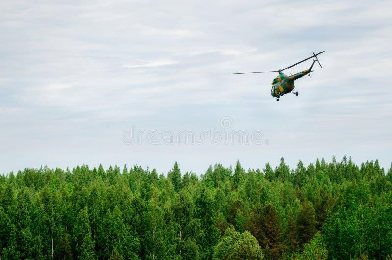 Kakifarbiger farbiger Hubschrauber fliegt in Himmel über Wald stockfoto