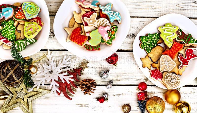 Kakor av julgingerbröd på tre plattor med träbord royaltyfri foto