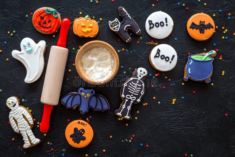 Kakor för den kockhalloween pepparkakan slår till, skelettet, spökesötsaker nära kavlen på svart copyspace för bästa sikt för bak royaltyfria bilder