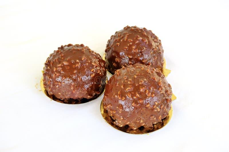 Kakor i formen av en boll som g?ras genomv?t i, mj?lkar choklad med muttrar p? en vit bakgrund arkivfoton