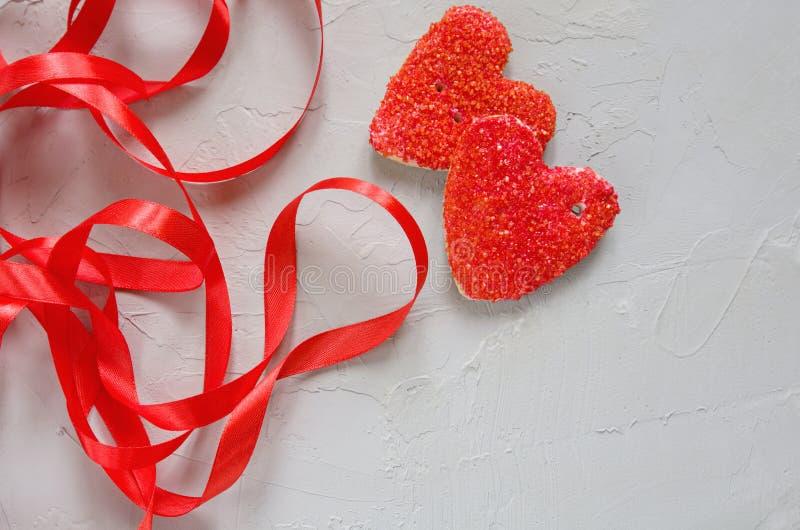 Kakor i formen av en röd hjärta med ett band på en grå bakgrund Valentin dag och romantiker arkivfoton