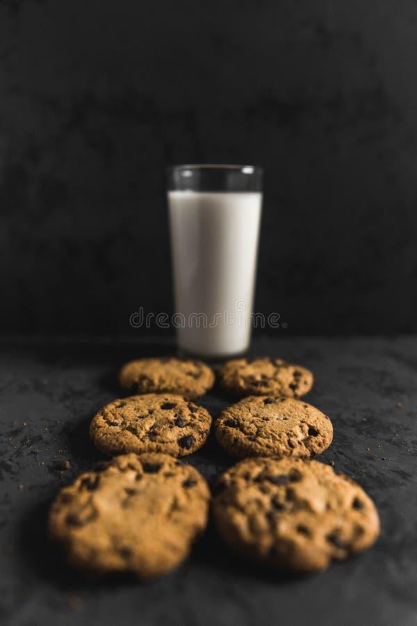 Kakor med chokladskepp och att mjölka med en mörk bakgrund arkivfoto