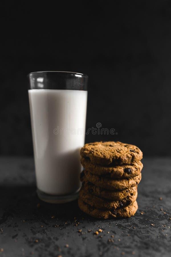 Kakor med chokladskepp och att mjölka med en mörk bakgrund arkivbild