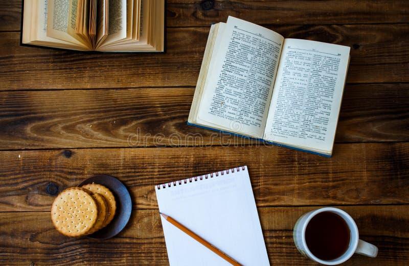 Kakor och den öppna boken för te ritar anteckningsboken på träbakgrund royaltyfri foto