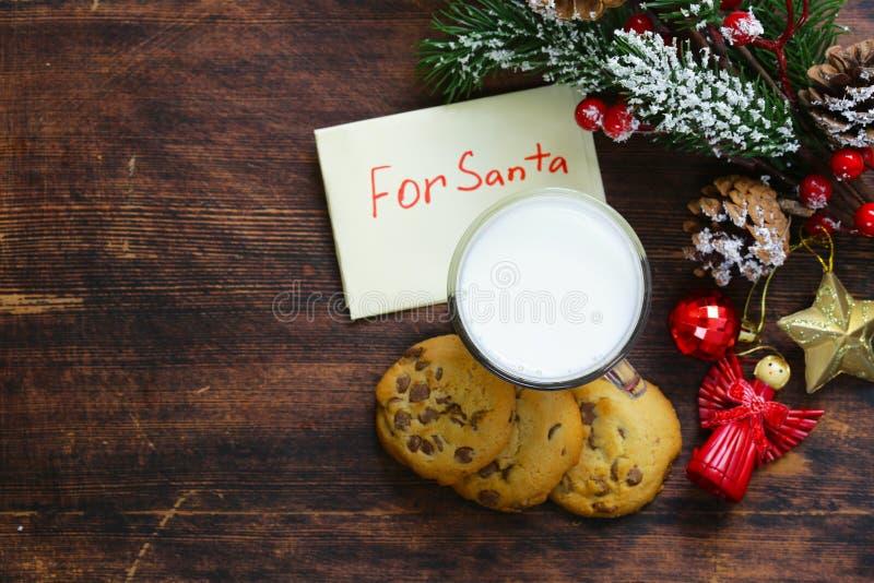 Kakor och ett exponeringsglas av mjölkar för jultomten arkivbilder