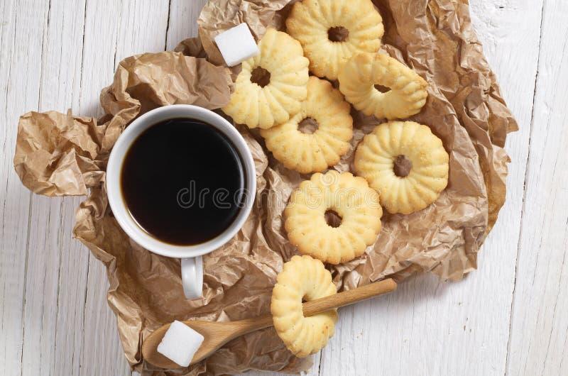 Kakor och kaffe på skrynkligt papper arkivfoton